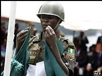 Un Soldat Nigerian descend le drapeau