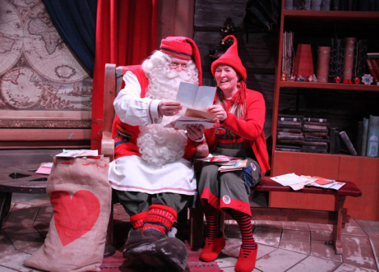 Santa Clause and elf named Rita Matila are reading the letters sent by Chinese children. (Photo by Guan Kejiang from People's Daily)