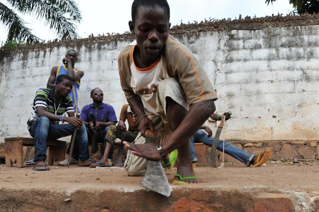 Un milicien anti-Balaka dépoussière sa machette en Centrafrique. Crédits : Sources