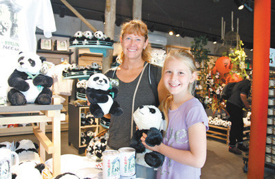 Tourists from Denmark are delightedly selecting Chinese panda themed souvenirs in a gift shop of the Berlin Zoo. (Photo by Guan Kejiang from People's Daily)