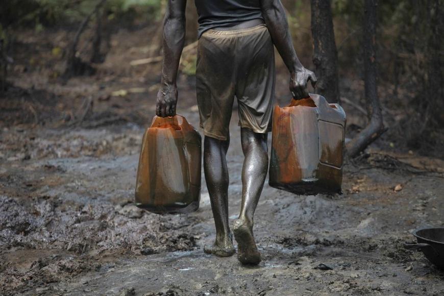 """Dans une raffinerie illégale. Au Nigeria, des milliers de personnes participent à ce détournement de pétrole, connu localement sous le nom de """"bunkering"""", qui consiste à trouer les pipelines pour voler du pétrole brut, qu'ils raffinent ou vendent directement. REUTERS/AKINTUNDE AKINLEYE"""