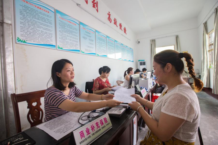"An employee working with the ""one-stop"" health care settlement center in Wan'an county, Jiangxi Province is handling the settlement procedures for impoverished household, August 7, 2017. (Photo by People's Daily Online)"