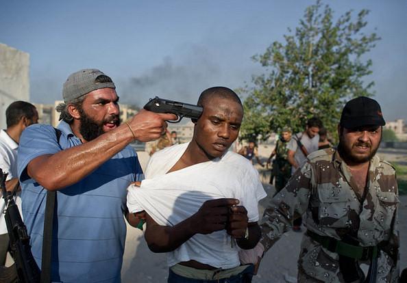 Un milicien libyen pointe son pistolet sur la tête d'un migrant. Crédits photo : sources