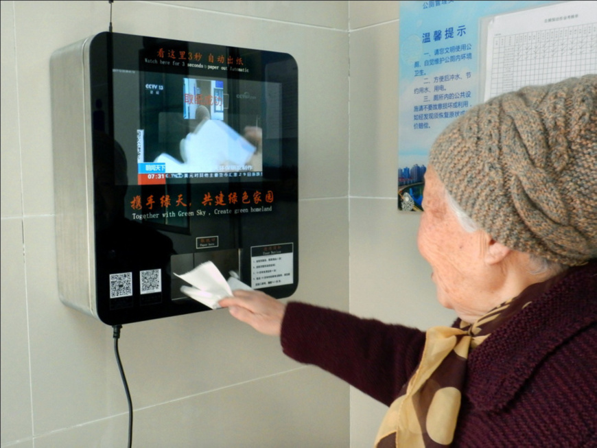 A resident scans her face for toilet paper at a public restroom in Nanjing, capital of east China's Jiangsu province, December 23, 2017. The newly-established facial recognition machine attracted many curious citizens to experience. (Photo from CFP)