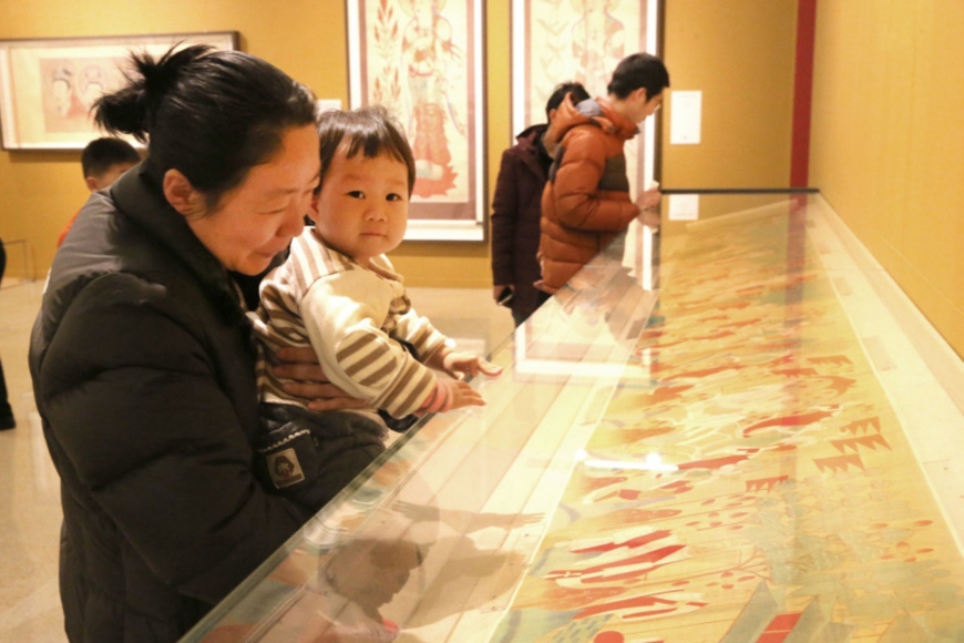 A woman takes her child to the Zhang Daqian Art Exhibition hosted by the National Museum of China, Sichuan Museum, and Rong Bao Zhai folk art gallery. More than 100 masterpieces of Zhang's artworks were exhibited. (Photo by CFP)