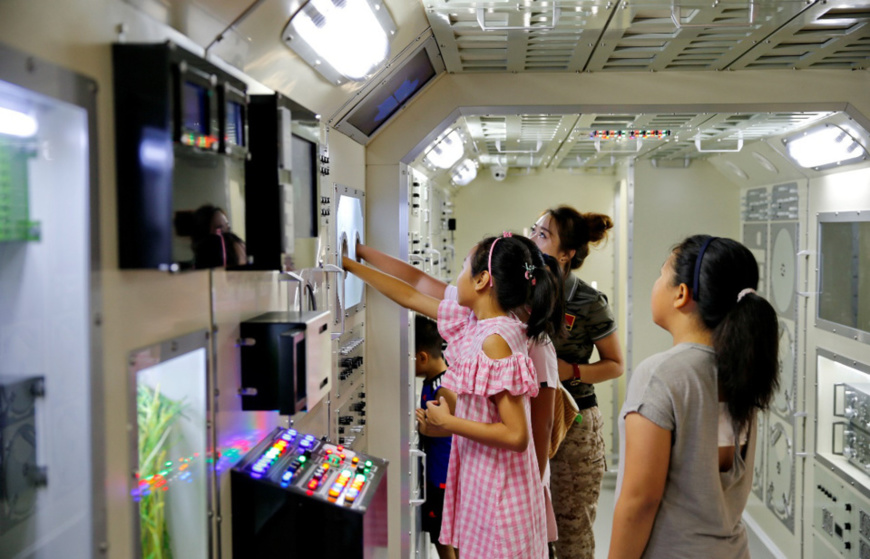 Children experience a simulated cabin of Tiangong-1 space lab at a virtual reality education base of military science in Qinhuangdao, northern China's Hebei province on Aug. 15, 2017. (Photo: CFP)