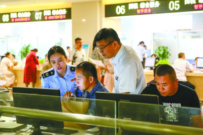 Staff of a service center in Fuyang, east China's Anhui province is helping residents with procedures, September 13, 2017. The city commits to better serving citizens by simplifying procedures, delegating power, innovating administrative management, transforming functions of government, and further stimulating market vitality. (Photo by Fan Bowen from People's Daily)
