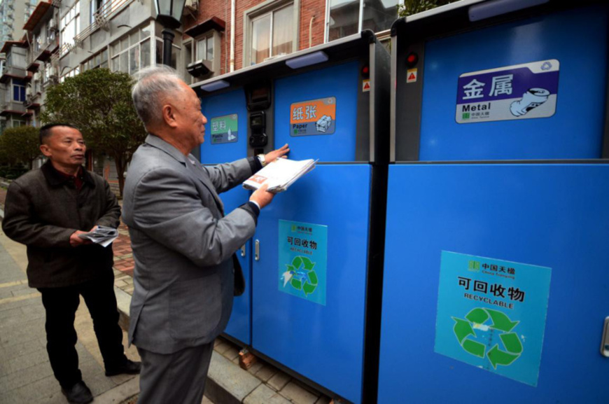 A resident throws rubbish into a garbage sorting can in Nanchang, east China's Jiangxi province, March 6, 2018. He will receive credits if he throws the trash into the right can, and the credits can be used to buy drinks, tissues and soaps. (Photo from CFP)