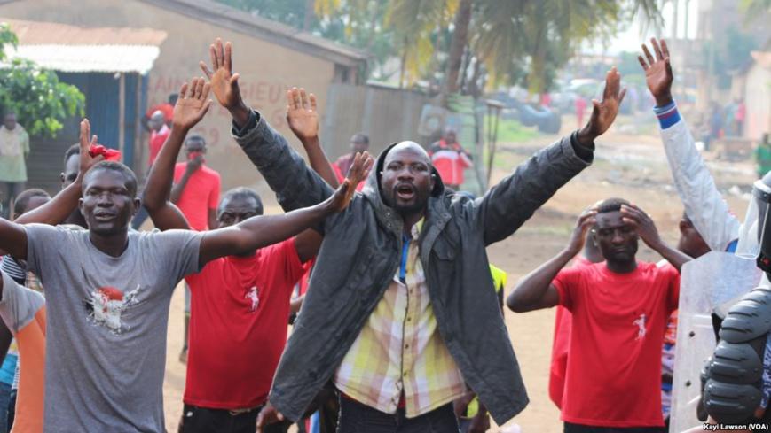 Mains levées, quelques manifestants essaient d'entamer une marche avant d'être dispersés à Lomé, Togo, 19 août 2017. (VOA/Kayi Lawson)