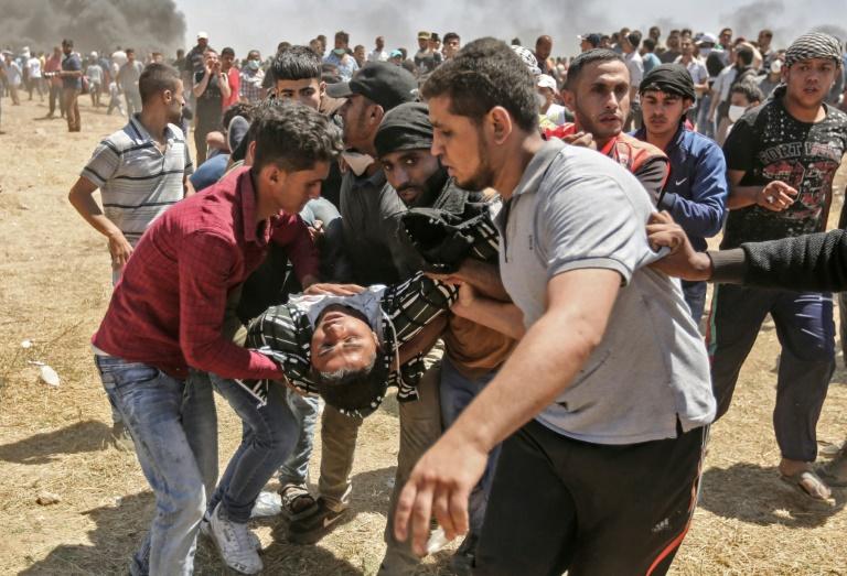 Un Palestinien blessé par des tirs israéliens est évacué par d'autres manifestants, le 14 mai 2018 dans la bande de Gaza, à la frontière avec Israël / © AFP / MAHMUD HAMS