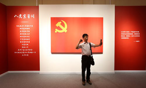 A visitor takes a selfie while pretending to take the oath to join the Party during an exhibition marking the 95th founding anniversary of the Party in Shanghai, July 26, 2016. Photo: VCG