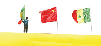 Chinese and Senegalese national flags fly on the National Wrestling Arena, built with Chinese assistance, to greet Chinese President Xi Jinping's arrival. (By Li Zhiwei from People's Daily)