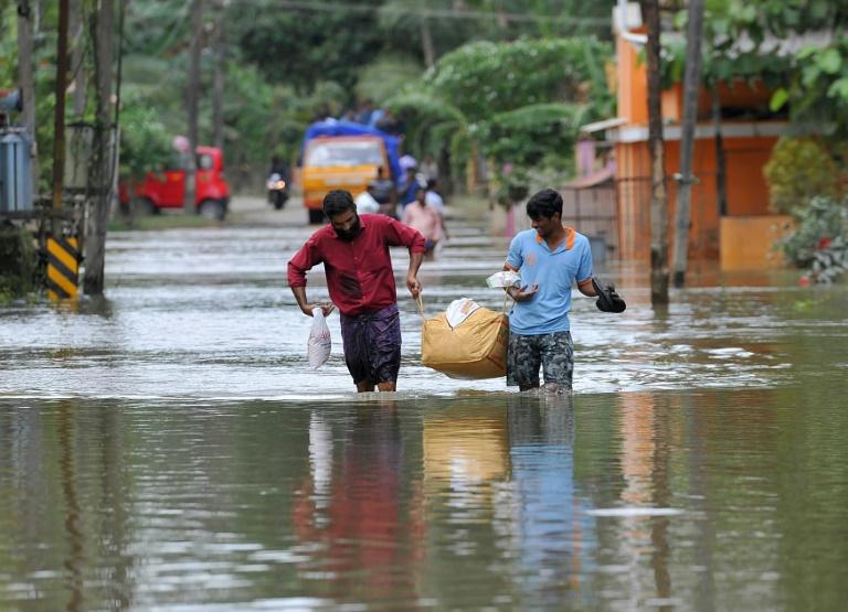 Des Indiens transportent de la nourriture et de l'eau pour les déplacés des inondations, dans le district d'Alappuzha, dans l'état indien du Kerala, le 21 août 2018 / © AFP/Archives / MANJUNATH KIRAN