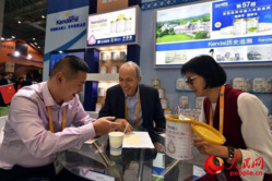 McMahon (central) and his Chinese partners talk about details of a product. Photo by Weng Qiyu from People's Daily Online