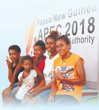 PNG citizens pose for pictures by an advertising board of APEC. Photo from Xinhua News Agency