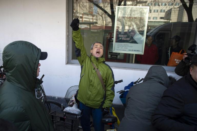 Le militant Yang Chunlin (c) crie son soutien à Me Wang Quanzhang devant le tribunal de Tianjin où se déroule le procès de l'avocat, le 26 décembre 2018 en Chine / © AFP / Nicolas ASFOURI