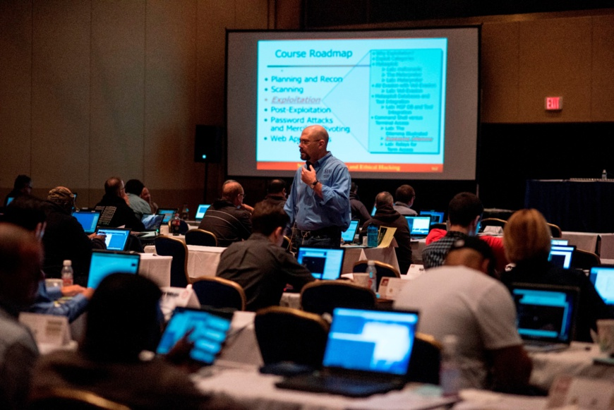 Participants listen to a global cyber security practitioner at a SANS training session.