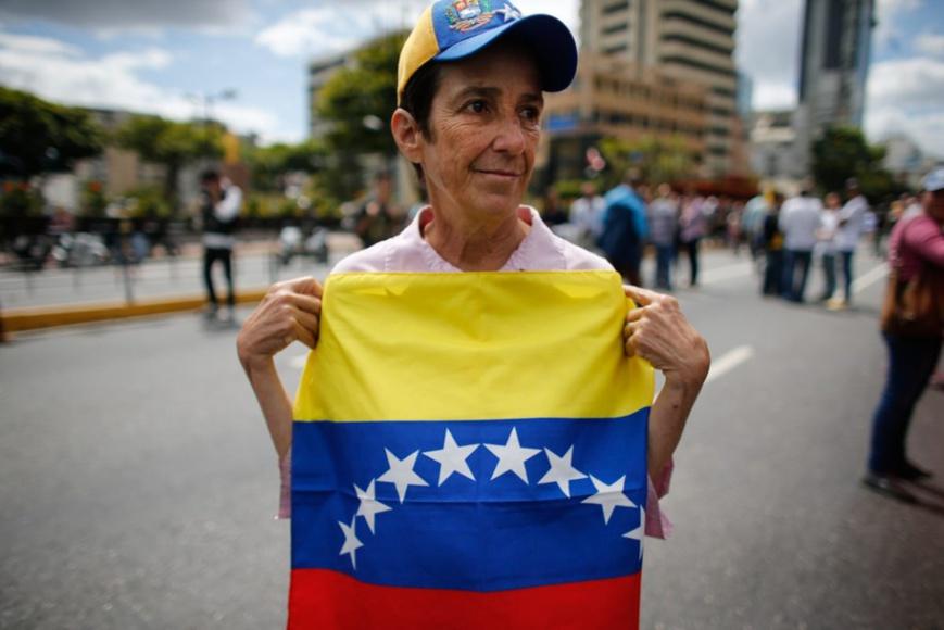 Une femme qui soutient Juan Guaido tient le drapeau national du Venezuela (© Ariana Cubillos/AP Images)