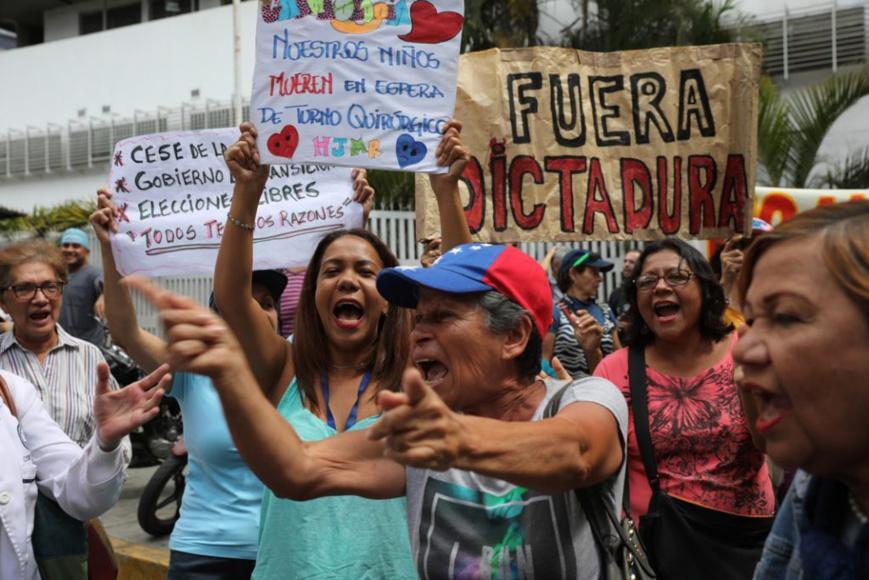 Des partisans de la démocratie brandissent des pancartes réclamant la fin du régime dictatorial de Maduro. (© Rodrigo Abd/AP Images)