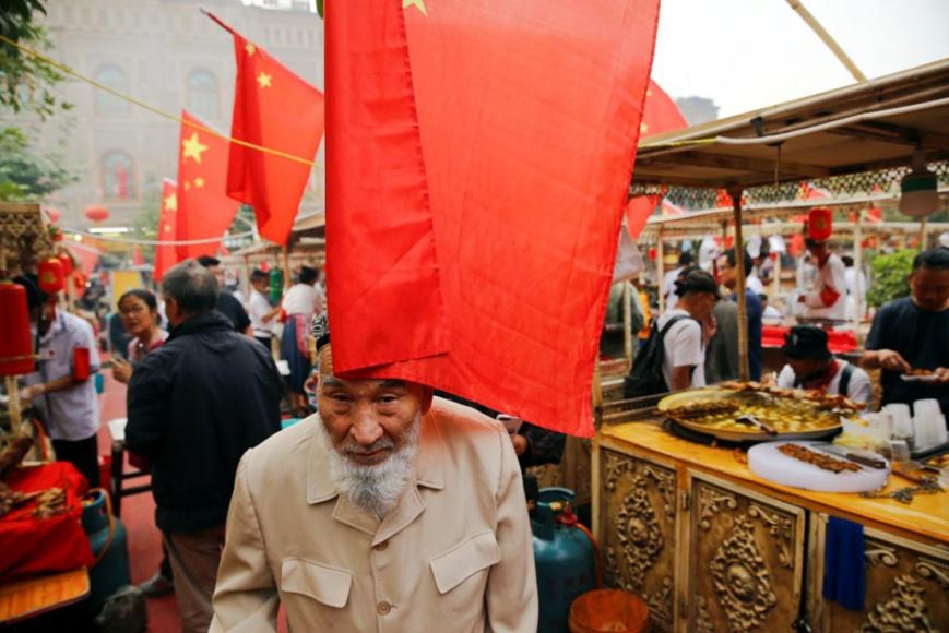 Des drapeaux chinois flottent au vent sur le marché dans la vieille ville de Kachgar, dans la province du Xinjiang. Photo du 6 septembre 2018. (© Thomas Peter/Reuters)