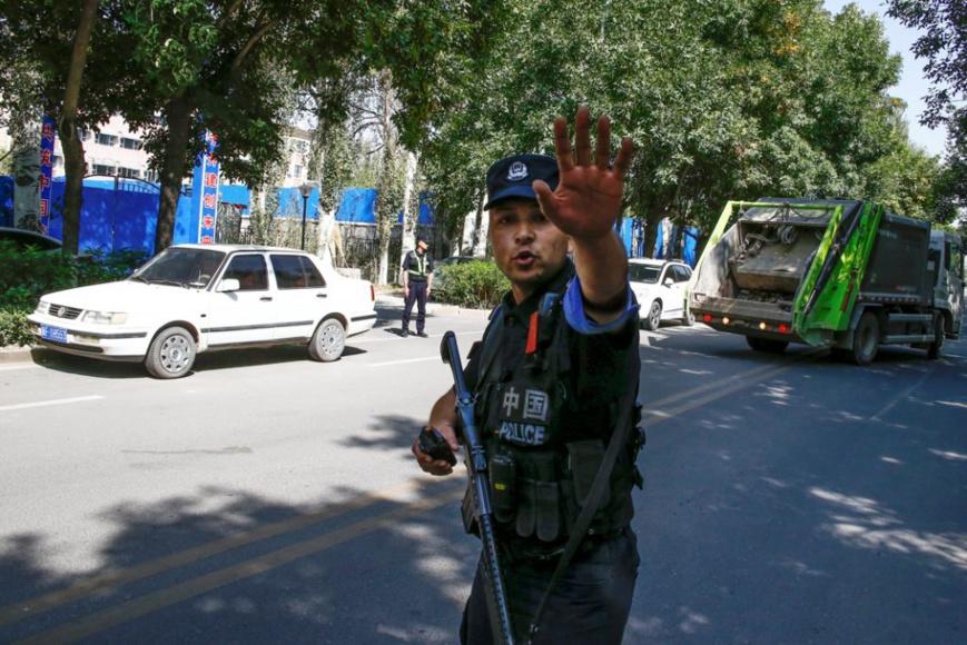 Un policier chinois ordonne à des reporters de ne pas avancer, à proximité d'un centre de détention au Xinjiang. (© Thomas Peter/Reuters)