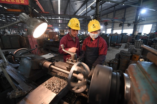 On February 25, 2019, Chen Ganfei, deputy to the National People's Congress and team leader of a lathe group in Jiangxi Gas Compressor Company, communicate with a co-worker over production techniques. (Photo by People's Daily)