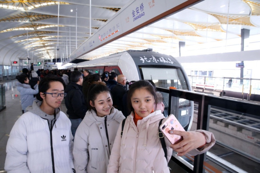 Citizens in Beijing take a selfie in front of a train which is entering the station along the maglev Line S1. Photo by People's Daily Online