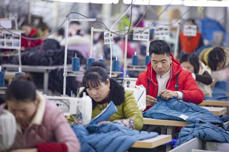 Migrant workers sew clothes at a factory in Shahe county, Ganyu district of Lianyungang, eastern China's Jiangsu province, March 3, 2019. (Photo by Zhang Guiliang, People's Daily Online)