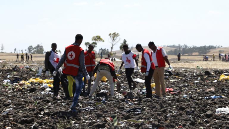 Des équipes de la Croix Rouge inspectant les débris du vol de la Ethiopian Airline qui s'est écrasé près d'Addis-Abeba (Ethiopie), le 10 mars 2019. (MICHAEL TEWELDE / AFP)