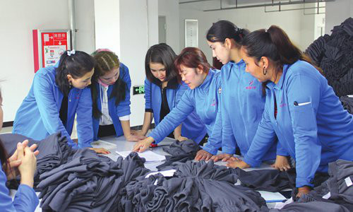 Workers in a clothing factory exchange experiences in Aksu prefecture, Northwest China's Xinjiang Uyghur Autonomous Region on February 19. Photo: Liu Xin/GT