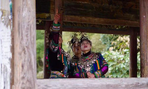 Members of Qixiannv are chatting on Fengyu Bridge, a unique architecture of the Dong ethnic group. (Photo from Global Times)