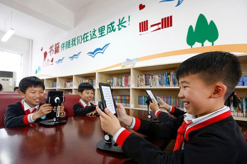 """On April 22, 2019, in order to welcome the arrival of """"world reading day"""", Jiangnan experimental primary school in Huangshan city, Anhui province, held the activity themed """"reading pleases heart & book campus"""". By reading picture books and e-readers, students will share the happiness of reading. (Photo by Shi Yalei from People's Daily online)"""