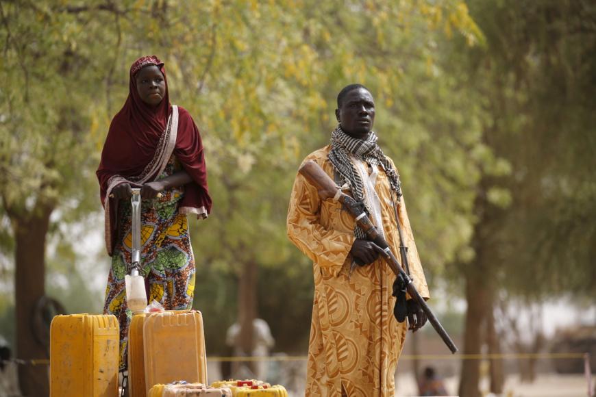 Un membre d'un groupe d'autodéfense civil tient un fusil de chasse tandis qu'une femme pompe de l'eau dans des jerrycans à Kerawa, Cameroun, 16 mars 2016. © REUTERS/Joe Penney