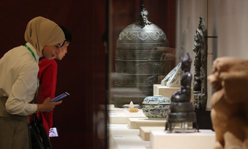 """Foreign visitors look at the cultural relics on display at """"The Splendor of Asia: An exhibit of Asian Civilizations,"""" which opened on Monday May 13 at Beijing's National Museum of China. Photo: VCG"""