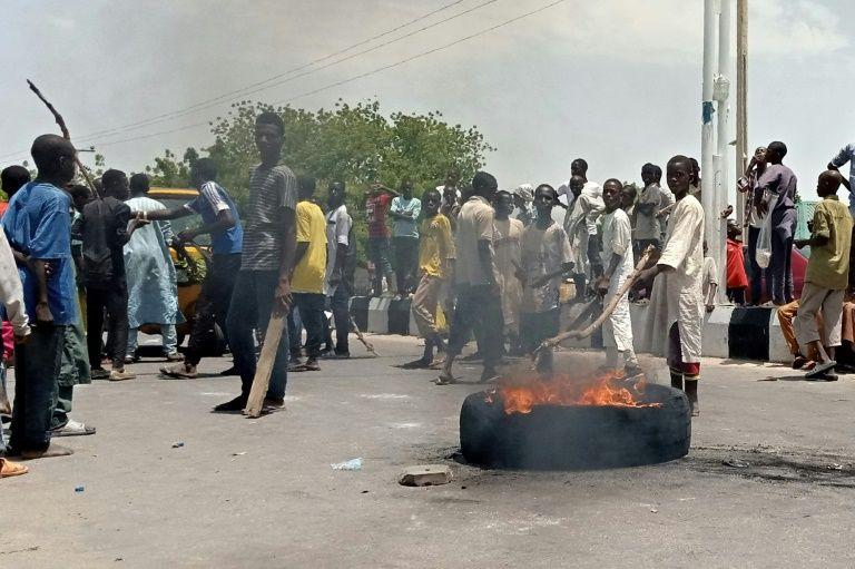 Des manifestants bloquent une route principale dans la ville nigériane de Maiduguri, au nord du pays, demandant aux autorités d'interdire une milice locale anti-Boko Haram qui, selon eux, les maltraite (AFP Photo/Audu MARTE)
