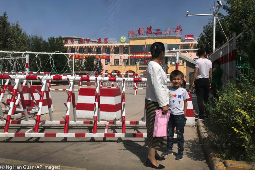 Les écoles fréquentées par les minorités au Xinjiang sont protégées par une kyrielle de caméras, de fils barbelés et de barrières. (© Ng Han Guan/AP Images)
