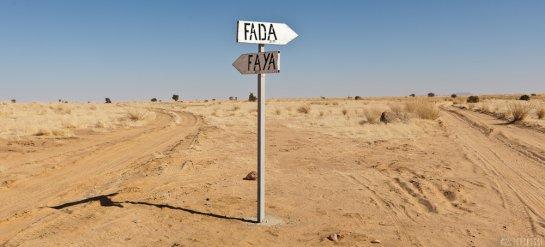 Illustration. Un panneau indiquant des directions vers les villes de Fada et Faya. © Tekenessi
