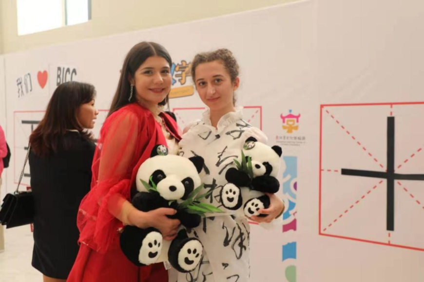 Greek citizens hold panda toys as they pose for a photo at a Chinese characters exhibition in Athens, Greece. (Photo by Hua Fang from People's Daily).