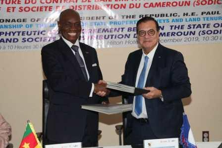 Echange de documents entre le ministre Henri Eyebe Ayissi (à gauche) et le PDG de Mercure Adnan  Houdrouge (à droite).