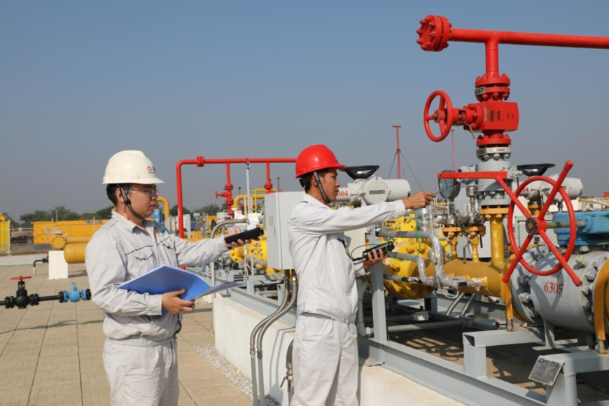 Chinese and Burmese workers test the equipment at the distribution station of China-Myanmar oil and gas pipelines in Mandalay, Myanmar. (Photo by Sun Guangyong from People's Daily)
