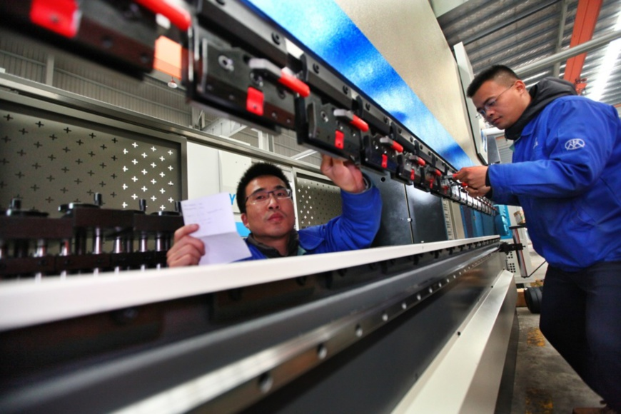 On Dec. 24, 2019, technicians assemble high-end CNC machine tools for export at a manufacturing workshop in Ma'anshan, east China's Anhui province. (Photo by Wang Wensheng, People's Daily Online)
