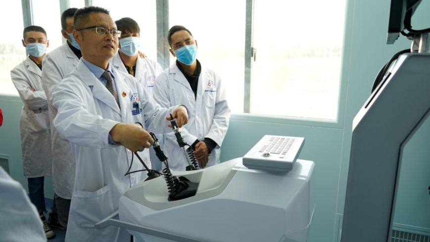 Guo Weigang, a doctor at Zhongshan Hospital, an affiliated hospital of Fudan University, performs a demonstration surgery at the Shigatse People's Hospital. (Photo by Shen Shaotie/People's Daily)