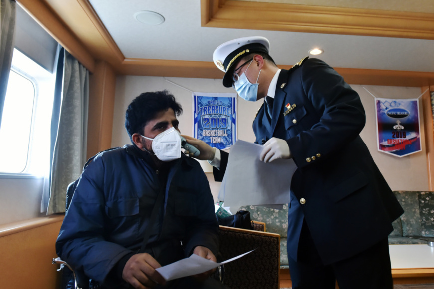 A customs officer in Changzhou, east China's Jiangsu province measures temperature for a foreign mariner, Jan. 30, 2020. Since China started the control and prevention of the novel coronavirus, the customs department of Changzhou resumed the health declaration form procedure and reinforced temperature monitoring and medical checks for entry-exit personnel. So far, 183 personnel on 9 vessels have been examined in total at waterway ports alone. (Photo by Xia Chenxi, People's Daily Online)