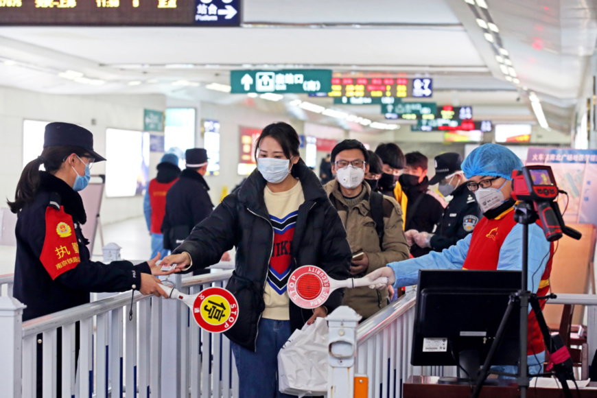 Photo taken on Feb. 2, 2020 shows policemen, medical staff and volunteers take passengers' body temperature and check identity information to prevent and control epidemic at the exit of a railway station in Changzhou, east China's Jiangsu province, where the passenger traffic increased gradually. Chen Wei/People's Daily Online