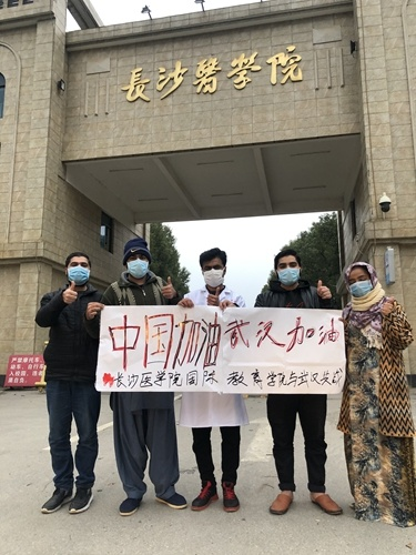Usman and his students from various countries at the campus of Changsha Medical University (CMU) hold a banner to cheer on Chinese amid the novel coronavirus outbreak. (Photo: Courtesy of CMU)