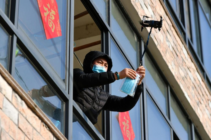 A man in home quarantine in Changping village, Jiapu town, Changxing county, Huzhou, east China's Zhejiang province, receives face masks and thermometer delivered by a drone on Feb.9, 2020. (Photo by Tan Yunfeng/People's Daily Online)