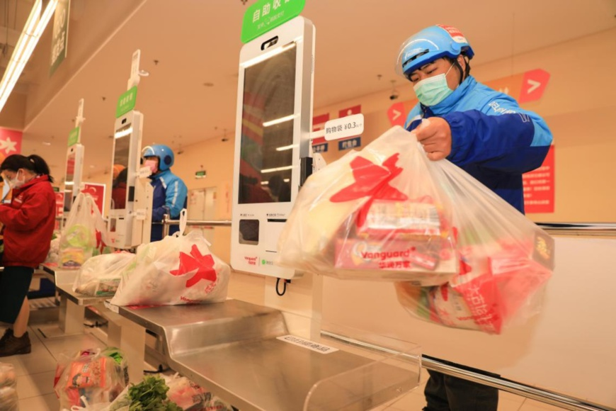 Couriers fetch commodities from a supermarket in Zhoushan, east China's Zhejiang province, Feb. 10, 2020. Photo by Chen Yongjian, People's Daily Online