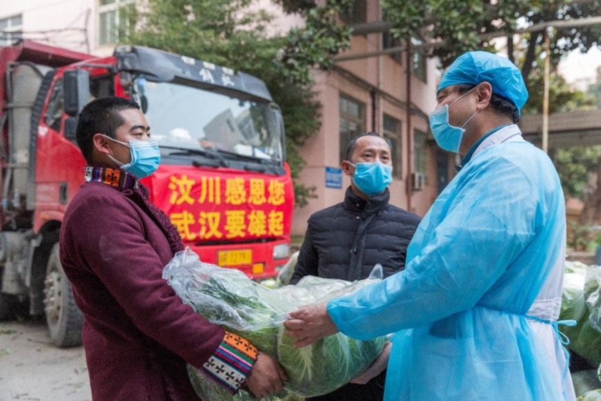 Zhao Yong, Chief of Longzhu village, Wenchuan county of Sichuan province and his fellow villagers deliver vegetables to a medical staff in Wuhan, Feb. 5. The man, together with 12 of his fellow villagers, have donated vegetables to 12 major hospitals in the city. (Photo by Zhang Wujun/People's Daily)