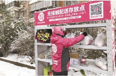 """A courier places grocery on a shelve at a residential complex in Beijing, Feb. 14. Online grocery delivery platforms have built """"non-contact"""" depositories in Beijing, Shanghai, and Guangzhou. Photo by People's Daily"""