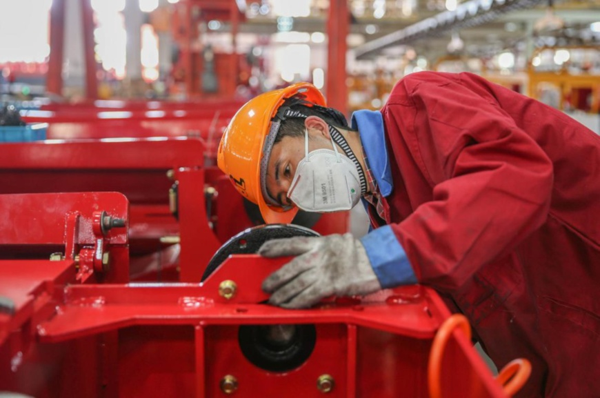 A technician of Zhejiang Dingli Machinery Co., Ltd. assembles and tests aerial work platforms in a general assembly workshop of the company, Feb. 20, 2020. The products will soon be exported to the U.S. (Photo by Yao Haixiang/People's Daily Online)